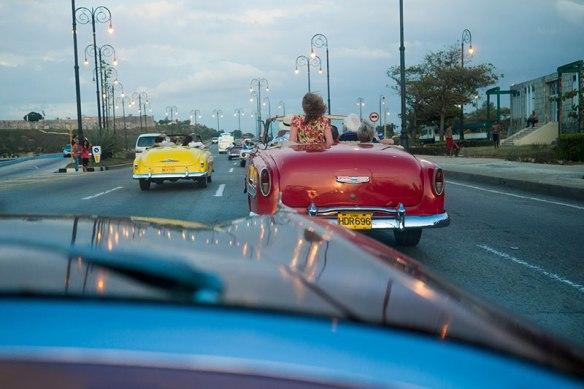 Tourists riding antique cars through Havana, Cuba.