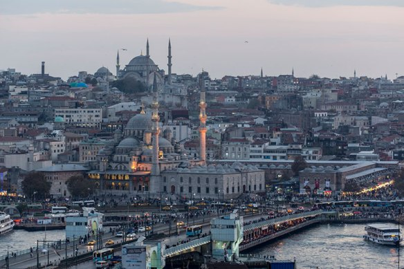 The New Mosque in the front and traffic on the Galata Bridge in Istanbul.